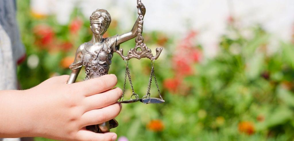 Barn håller i Justitiastaty